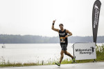 Man running in a 10 mile race in New Hampshire near a lake